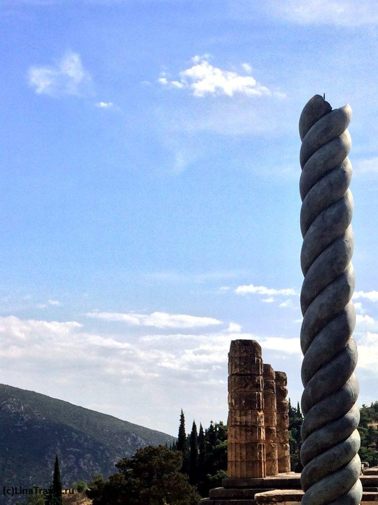 Половина античной Змеиной колонны на фоне храма Апполона в Дельфах.